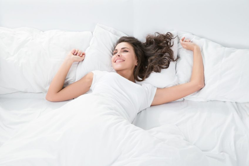 53057562 - young woman sleeping on the white linen in bed at home, top view